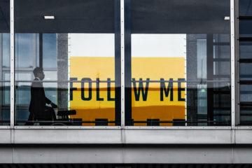Mann auf Gangway mit Follow Me Werbetafel